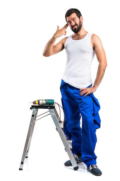 Giovane tecnico elettrico con un trapano che fa il gesto suicida Foto Gratuite