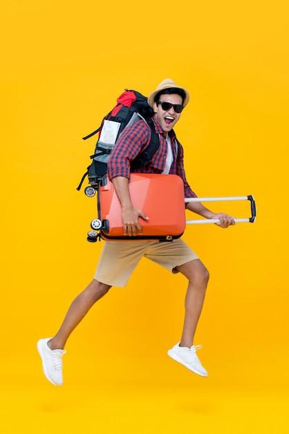 Giovane turista asiatico felice emozionante dell'uomo con il salto dei bagagli Foto Premium