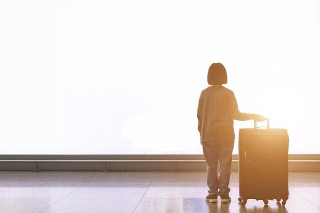 Giovane turista con bagagli che stanno davanti al grande tabellone per le affissioni della luce bianca all'aeroporto Foto Premium
