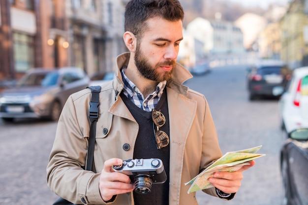 Giovane turista maschio alla ricerca di una strada con una mappa in mano in città Foto Gratuite
