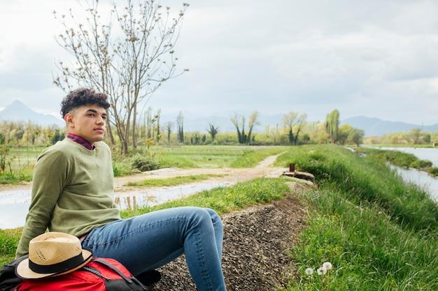 Giovane ubicazione maschio del viaggiatore bello sulla banca del fiume Foto Gratuite