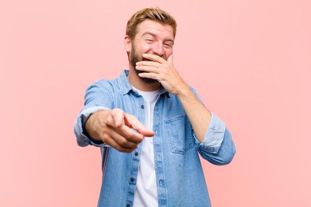 Giovane uomo adulto biondo che ride di te, indicando la macchina fotografica e prendendo in giro o prendendoti in giro Foto Premium