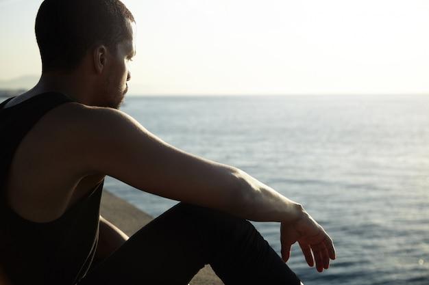 Giovane uomo africano che contempla paesaggio stupefacente del mare calmo Foto Gratuite
