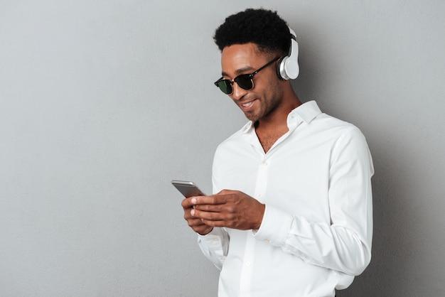 Giovane uomo africano felice nella musica d'ascolto degli occhiali da sole Foto Gratuite
