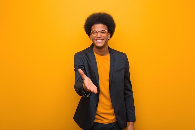 Giovane uomo afroamericano di affari sopra una parete arancione che raggiunge fuori per accogliere qualcuno Foto Premium