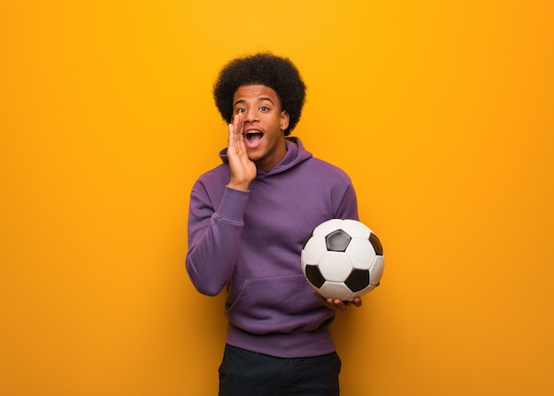 Giovane uomo afroamericano di sport che tiene un pallone da calcio che grida qualche cosa di felice alla parte anteriore Foto Premium