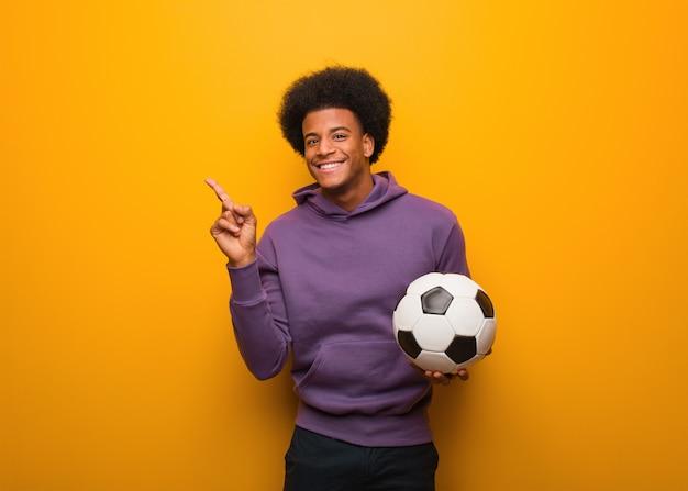 Giovane uomo afroamericano di sport che tiene un pallone da calcio che indica il lato con il dito Foto Premium