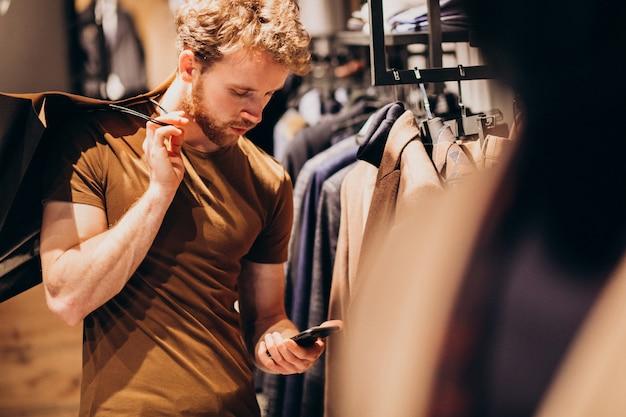Giovane uomo al negozio di abbigliamento maschile parlando al telefono Foto Gratuite