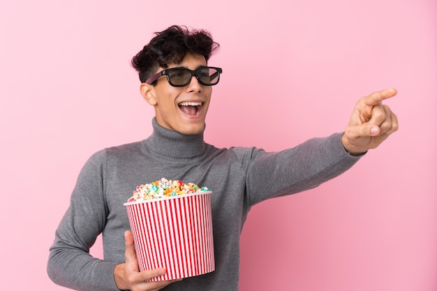 Giovane uomo argentino sopra la parete bianca isolata con gli occhiali 3d e tenendo un grande secchio di popcorn mentre punta lontano Foto Premium
