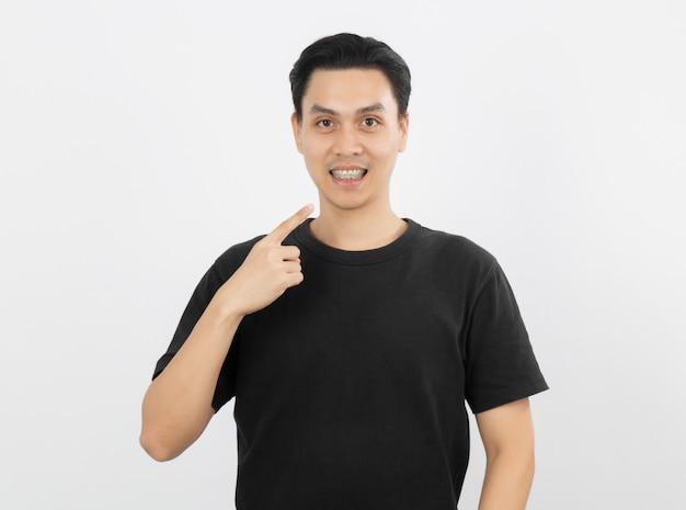 Giovane uomo asiatico bello che sorride con le parentesi graffe con indicare del dito isolato su bianco Foto Premium