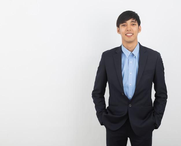 Giovane uomo asiatico bello di affari che guarda alla macchina fotografica isolata su bianco Foto Premium