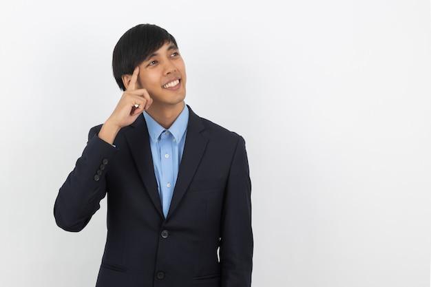 Giovane uomo asiatico bello di affari che pensa un'idea mentre cercando isolato su bianco Foto Premium