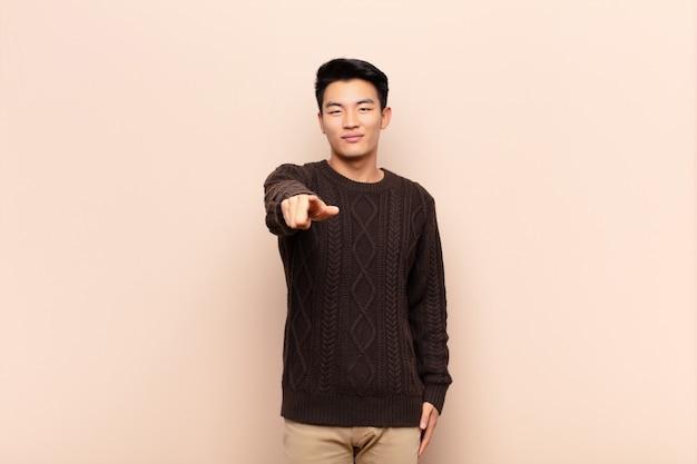 Giovane uomo asiatico che punta alla fotocamera con un sorriso soddisfatto, fiducioso, amichevole, scegliendovi sopra la parete di colore Foto Premium