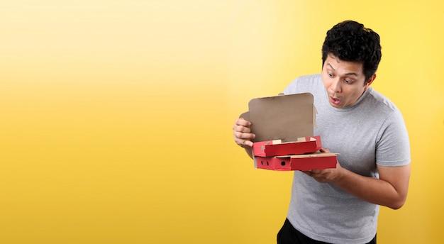 Giovane uomo asiatico che tiene la scatola di consegna con pizza italiana spaventato per lo shock con una faccia sorpresa, Foto Premium