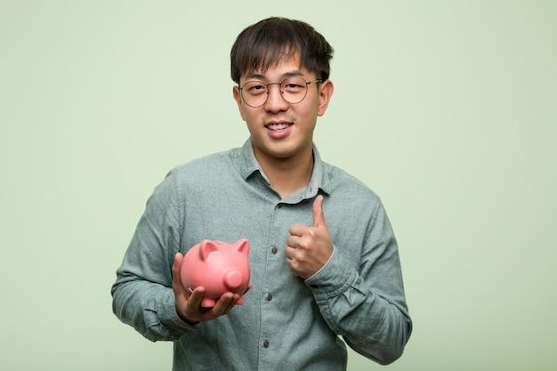 Giovane uomo asiatico che tiene un porcellino salvadanaio che sorride e che alza pollice in su Foto Premium