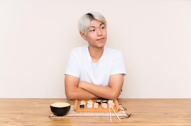 Giovane uomo asiatico con i sushi in una tavola che pensa un'idea Foto Premium