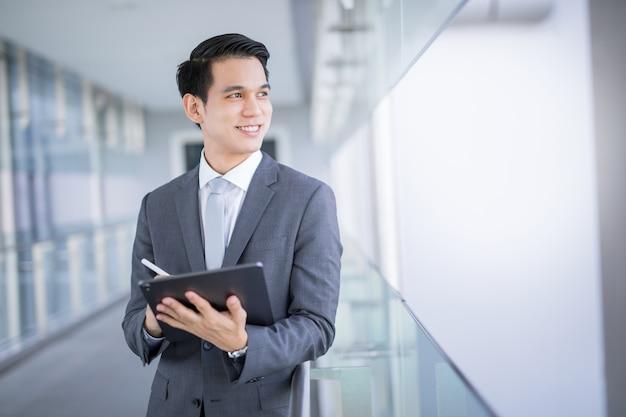 Giovane uomo asiatico di affari che tiene una compressa che osserva via Foto Premium