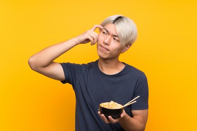 Giovane uomo asiatico sopra giallo isolato con dubbi e con espressione del viso confuso Foto Premium