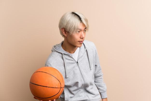 Giovane uomo asiatico sopra isolato con la palla di pallacanestro Foto Premium