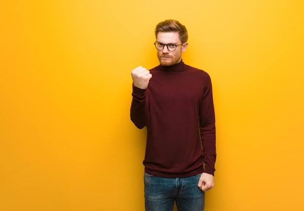 Giovane uomo astuto che mostra pugno alla fronte, espressione arrabbiata Foto Premium