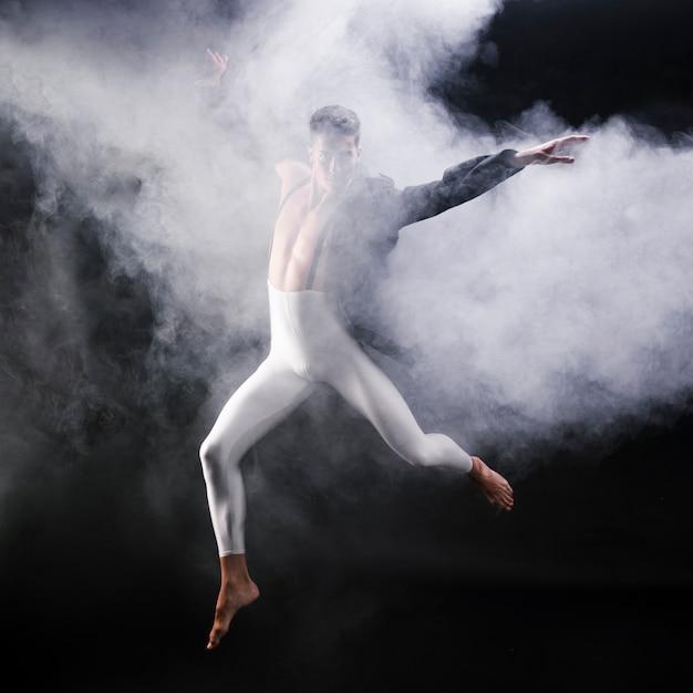 Giovane uomo atletico che salta e che balla vicino al fumo Foto Gratuite
