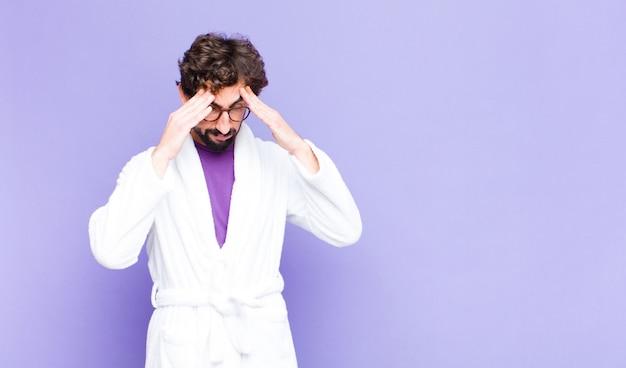 Giovane uomo barbuto che indossa accappatoio cercando stressato e frustrato, lavorando sotto pressione con un mal di testa e turbato da problemi Foto Premium