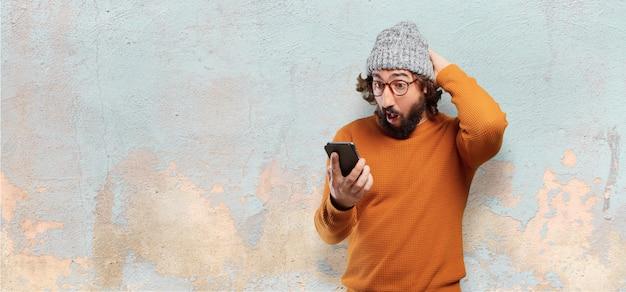 Giovane uomo barbuto con uno smart phone Foto Premium
