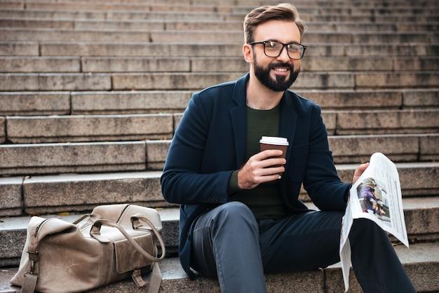 Giovane uomo barbuto felice che si siede all'aperto sui punti Foto Gratuite