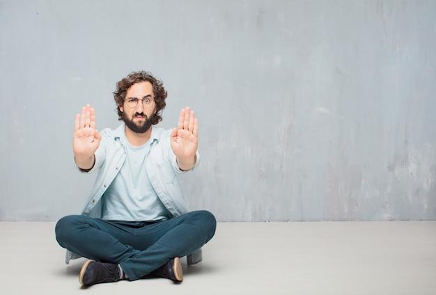 Giovane uomo barbuto freddo che si siede sul pavimento. fondo della parete del grunge Foto Premium