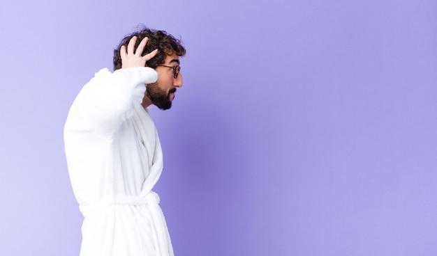 Giovane uomo barbuto pazzo che indossa accappatoio contro la parete dello spazio di copia Foto Premium