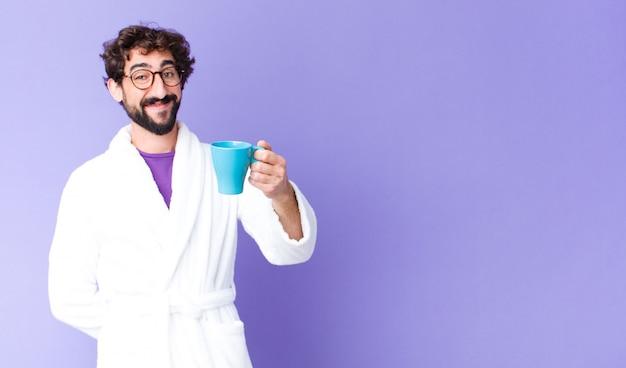 Giovane uomo barbuto pazzo che indossa accappatoio e avendo un caffè Foto Premium