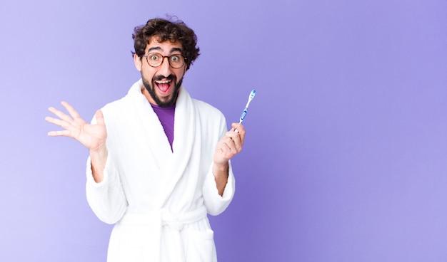 Giovane uomo barbuto pazzo che indossa accappatoio e spazzolino da denti. Foto Premium