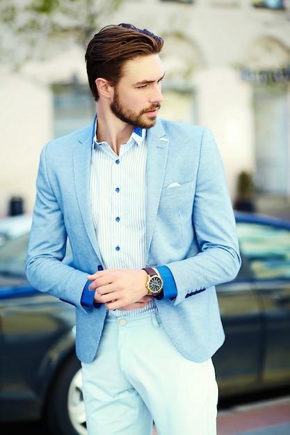 Giovane uomo bello alla moda in tuta in strada Foto Gratuite