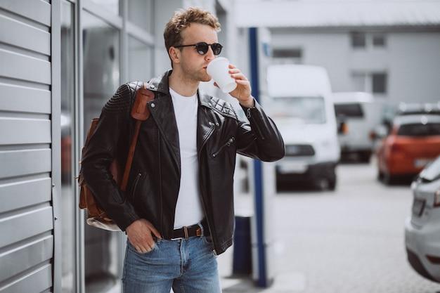 Giovane uomo bello bere caffè in strada Foto Gratuite