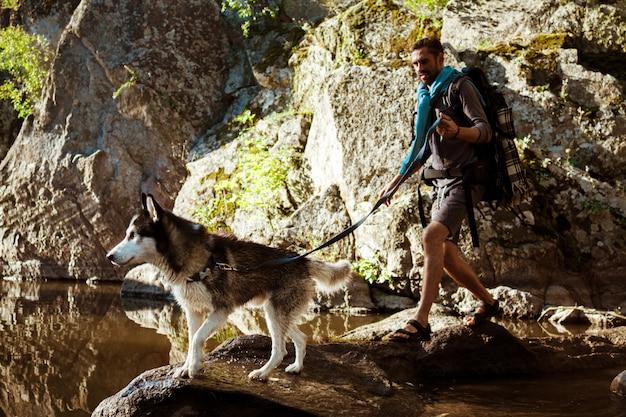Giovane uomo bello che cammina con il cane husky nel canyon vicino all'acqua Foto Gratuite