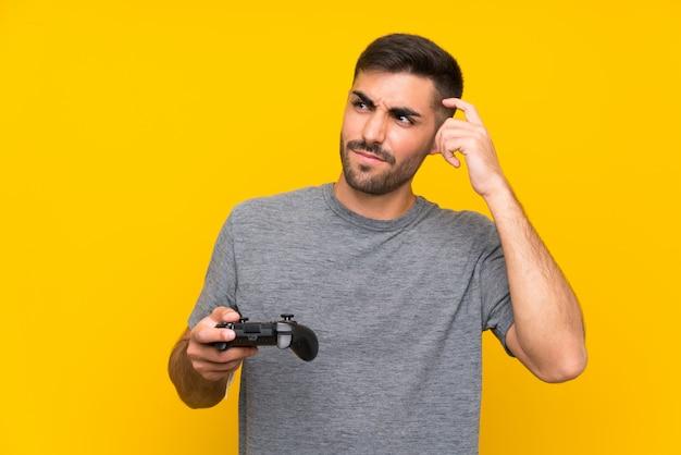 Giovane uomo bello che gioca con un controller di videogioco sul muro giallo isolato con dubbi e con espressione faccia confusa Foto Premium