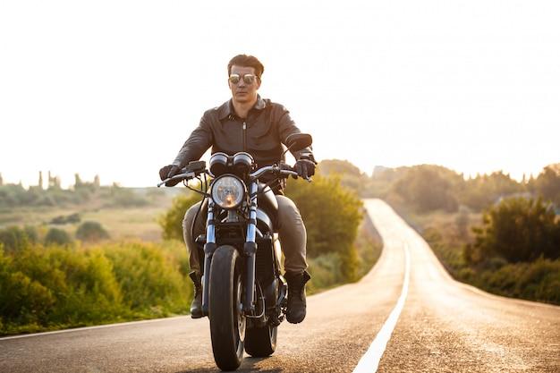 Giovane uomo bello che guida su una moto a strada di campagna. Foto Gratuite