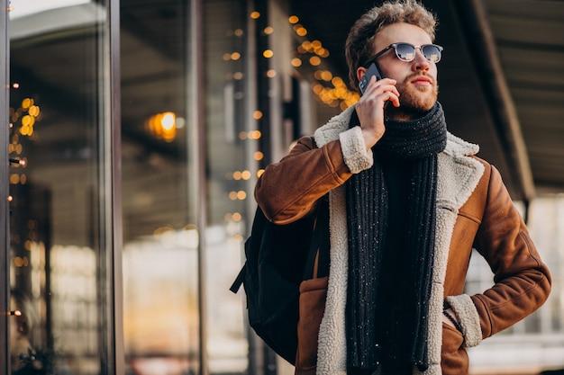 Giovane uomo bello che parla sul telefono dall'aeroporto Foto Gratuite
