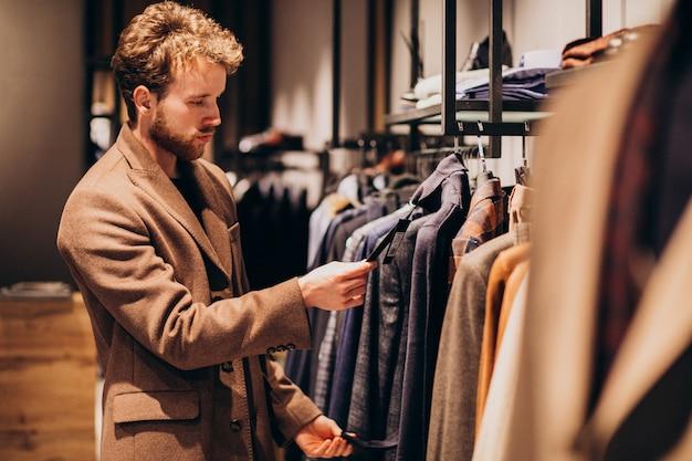 Giovane uomo bello che sceglie i vestiti al negozio Foto Gratuite