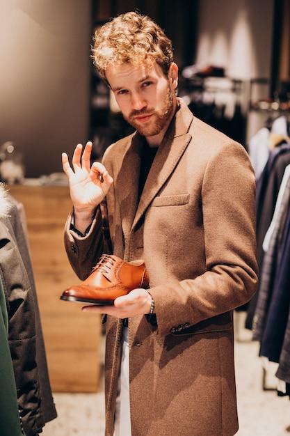 Giovane uomo bello che sceglie le scarpe ad un negozio Foto Gratuite
