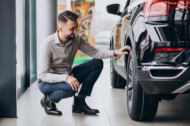 Giovane uomo bello che sceglie un'automobile in una sala d'esposizione dell'automobile Foto Gratuite