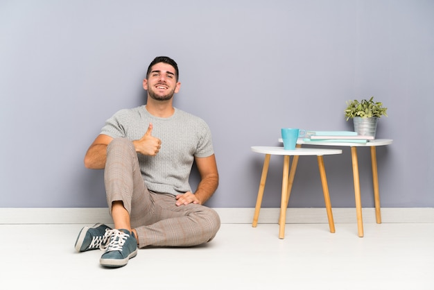 Giovane uomo bello che si siede sul pavimento dando un pollice in alto gesto Foto Premium
