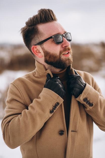 Giovane uomo bello che sta nel parco di inverno, ritratto Foto Gratuite
