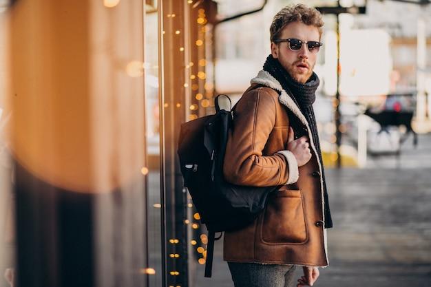 Giovane uomo bello con abiti invernali e zaino Foto Gratuite