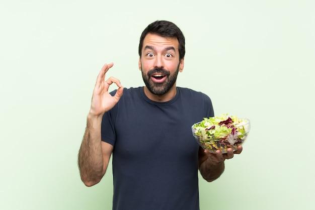 Giovane uomo bello con insalata sopra la parete verde isolata sorpresa e mostrando segno giusto Foto Premium