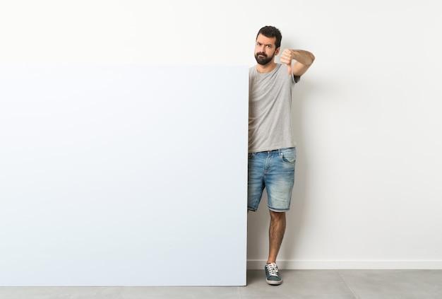 Giovane uomo bello con la barba che tiene un grande cartello vuoto blu che mostra pollice giù con l'espressione negativa Foto Premium