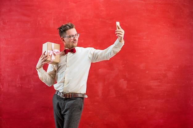 Giovane uomo bello con regalo e telefono Foto Gratuite