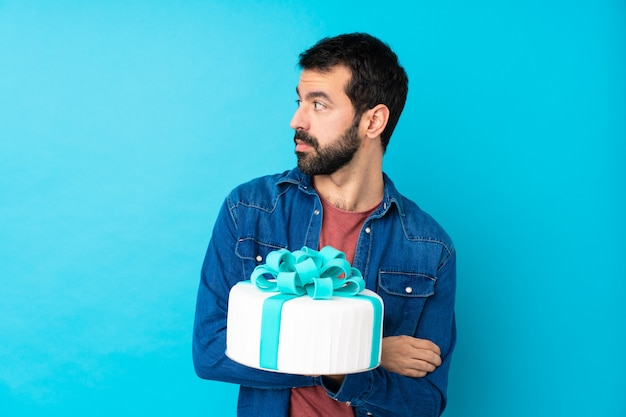 Giovane uomo bello con una grande torta sopra il ritratto blu isolato della parete Foto Premium