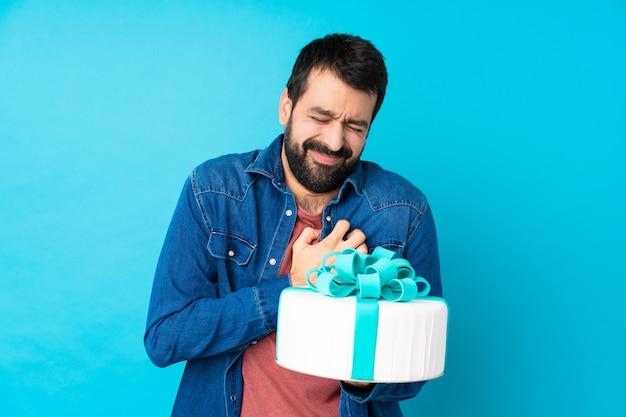 Giovane uomo bello con una grande torta sopra la parete blu isolata che ha un dolore nel cuore Foto Premium