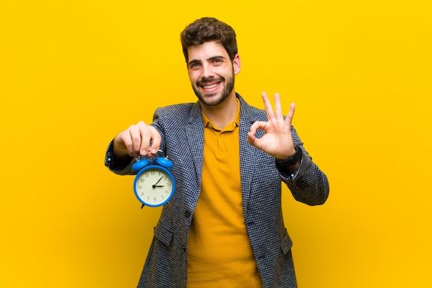 Giovane uomo bello con una sveglia su sfondo arancione Foto Premium